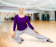 Charming beautiful elderly woman doing exercises while working out playing sports Stock Images
