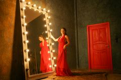 Charming beautiful girl in a red long luxury  evening dress on a fur rug near a huge mirror in a frame with bulbs. Charming beautiful girl in a evening dress on royalty free stock images