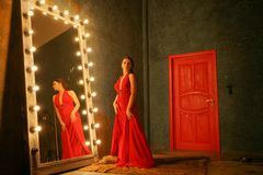 Charming beautiful girl in a red long luxury  evening dress on a fur rug near a huge mirror in a frame with bulbs. Charming beautiful girl in a evening dress on stock photography