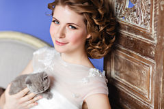 Charming and beautiful girl in white dress sitting on a sofa on royalty free stock image