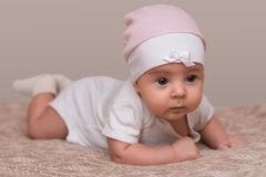 Charming beautiful lovely small female baby with plump cheeks creeps on bed, looks innocently on something, being naughty. Cute ba. By infant plays alone Royalty Free Stock Photo