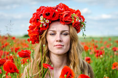 Charming beautiful sexy girl with long hair and gorgeous makeup walks on a poppy field holding a bouquet of red poppies Royalty Free Stock Photos