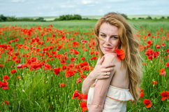 Charming beautiful sexy girl with long hair and gorgeous makeup walks on a poppy field holding a bouquet of red poppies Stock Image