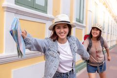 Charming beautiful traveler woman is holding hand's friend and inviting friend to some touristic place. They look happiness and royalty free stock images