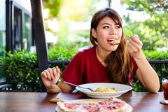 Charming beautiful woman is enjoying her Italian meal at a restaurant. Attractive beautiful girl looks so happy and satisfied the royalty free stock images