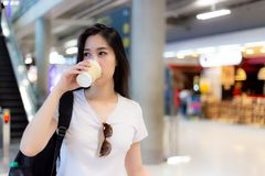 Charming beautiful woman hold paper cup of coffee and drink back stock photography