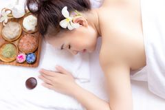 Charming beautiful woman lying down on bed, feels relaxed, comfortable, happy at aromatherapy, spa shop with herbal background. P royalty free stock photo