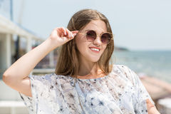 Charming and beautiful young model girl in sun glasses on the sea background. A cute female model. Beautiful girl in sun glasses. royalty free stock image