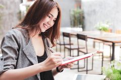 Charming beautiful young woman is checking dinner reservations o stock image