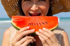 Charming beautiful young woman eating watermelon to cool down and quench her thirst in summer season at beach. It look juicy and royalty free stock photo