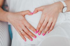 Charming tummy which the pregnant woman in a white dress embraces. The pregnant girl with pink manicure embracing belly royalty free stock image