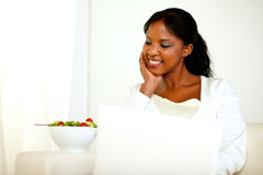 Charming black woman looking down to her salad. Portrait of a charming black woman looking down to her salad while is sitting on sofa in front of her laptop Stock Photos