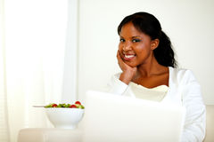 Charming black woman looking and smiling at you. Portrait of a charming black woman looking and smiling at you with a salad bowl while is sitting on sofa in Stock Image