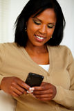 Charming black woman sending message by cellphone Royalty Free Stock Images