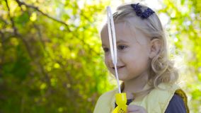Charming blond girl staying in sunrays and blowing soap bubbles. Little child with brown eyes playing in the park and. Smiling stock video footage