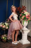 Charming blond girl in a white dress with a peach. Next to vases of flowers royalty free stock photos