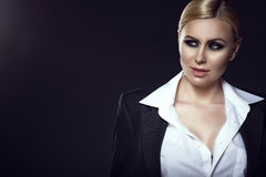 Charming blond model in white male shirt and jacket looking aside with a grin. Close up portrait of charming blond model with pulled back hair and smoky eye make Stock Photography