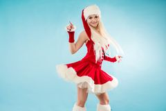 Charming blond woman in Christmas outfit. Red Santa suit with hood. Charming blond woman in Christmas outfit. Red Santa suit with hood, blue background Royalty Free Stock Photo