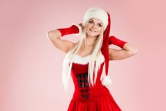 Charming blond woman in Christmas outfit. Red Santa suit with hood. Charming blond woman in Christmas outfit. Red Santa suit with hood, pink background Stock Photos