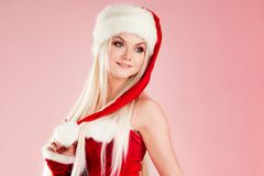 Charming blond woman in Christmas outfit. Red Santa suit with hood. Charming blond woman in Christmas outfit. Red Santa suit with hood, pink background Stock Photo