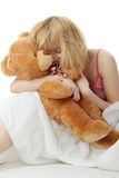 Charming blonde. In bed embraces teddy bear isolated Stock Image