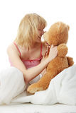 Charming blonde. In bed embraces teddy bear isolated Royalty Free Stock Image