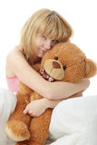 Charming blonde. In bed embraces teddy bear isolated Royalty Free Stock Images