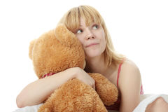 Charming blonde in bed. Embraces teddy bear isolated Royalty Free Stock Photos