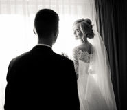 Charming blonde bride looks over her shoulder at groom Stock Photography