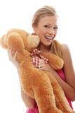 Charming blonde embraces teddy bear  Stock Photo
