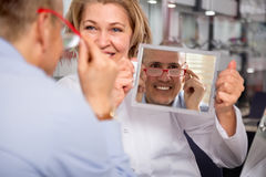 Charming blonde female optician consulting male customer about f Royalty Free Stock Photo