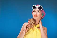 Charming blonde girl in vintage yellow dress and sunglasses over blue background. Stock Photos