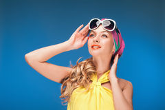 Charming blonde girl in vintage yellow dress and sunglasses over blue background. Royalty Free Stock Photography