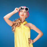 Charming blonde girl in vintage yellow dress and sunglasses over blue background. Royalty Free Stock Photo