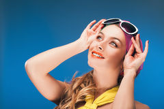 Charming blonde girl in vintage yellow dress and sunglasses over blue background. Stock Photography