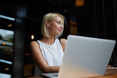 Charming blonde lady with good mood enjoying leisure while sitting with laptop computer in modern coffee shop,. Young beautiful female using portable net-book Royalty Free Stock Photo
