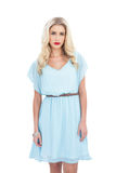 Charming blonde model in blue dress looking at camera Royalty Free Stock Photography