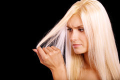 Charming blonde is not happy with fragile hair. It is isolated on black background royalty free stock images