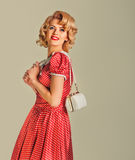 Charming blonde pin-up girl with little bag Royalty Free Stock Image