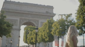 Charming blonde posing near the Arc de Triomphe in Paris. Charming blonde in sunglasses wearing a yellow dress posing near the Arc de Triomphe in Paris stock video footage
