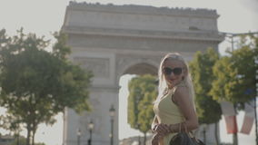 Charming blonde posing near the Arc de Triomphe in Paris. Charming blonde in sunglasses wearing a yellow dress posing near the Arc de Triomphe in Paris stock footage