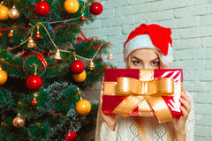 Charming blonde in santa hat hides her face behind a big Christm Royalty Free Stock Images