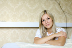 Charming blonde smiles and poses for camera, located in sleeping Stock Images