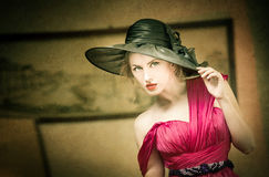 Charming blonde woman with black hat, retro image. Young beautiful fair hair female posing vintage. Mysterious lady