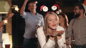 Charming blonde woman is blowing off bright shiny confetti on christmas party. Young woman is blowing away shiny tinsel from hands on Christmas party. Her stock video footage