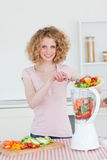 Charming blonde woman using a mixer in the kitchen Royalty Free Stock Photos