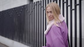 Charming blonde woman is wearing trendy mauve coat with fur collar, walking in city near building with fences stock video footage