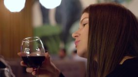 Charming blue-eyed brown-haired girl with a glass of red wine in her hands. Alcohol in the restaurant. stock video