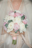Charming bouquet for the bride with pink peonies and eucalyptus. Charming and delicate bride holding bouquet with peonies and eucalyptus. Pink and white peonies Stock Image