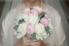 Charming bouquet for the bride with pink peonies and eucalyptus. Charming and delicate bride holding bouquet with peonies and eucalyptus. Pink and white peonies Stock Photo